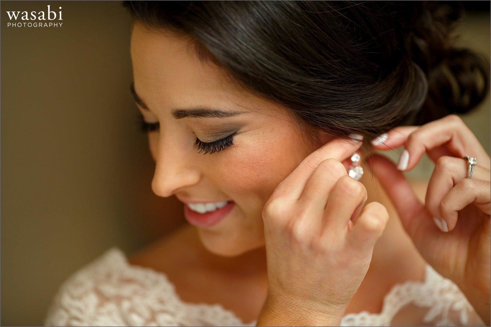 bride putting on earring wedding photos