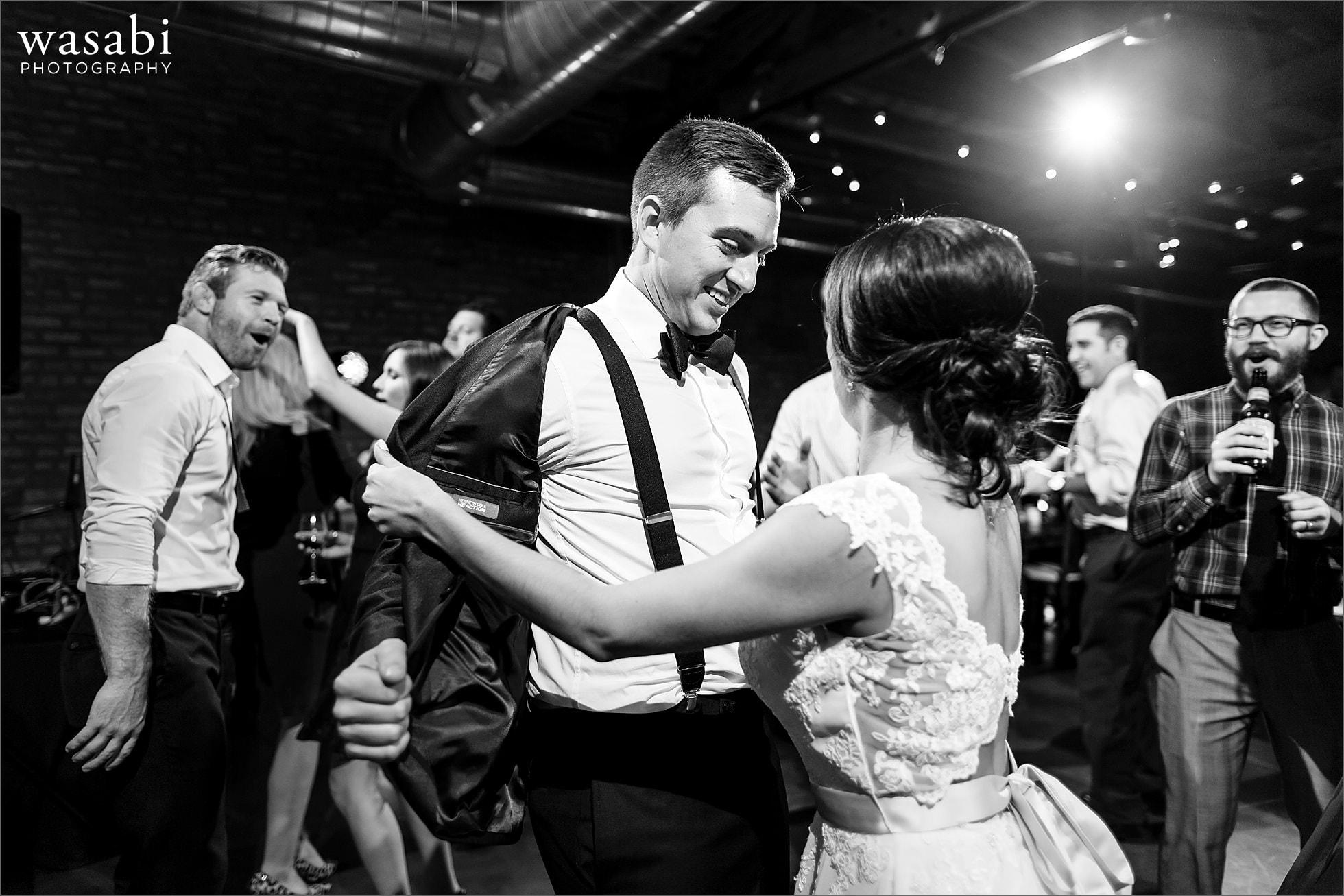 bride takes off grooms jacket on dancefloor