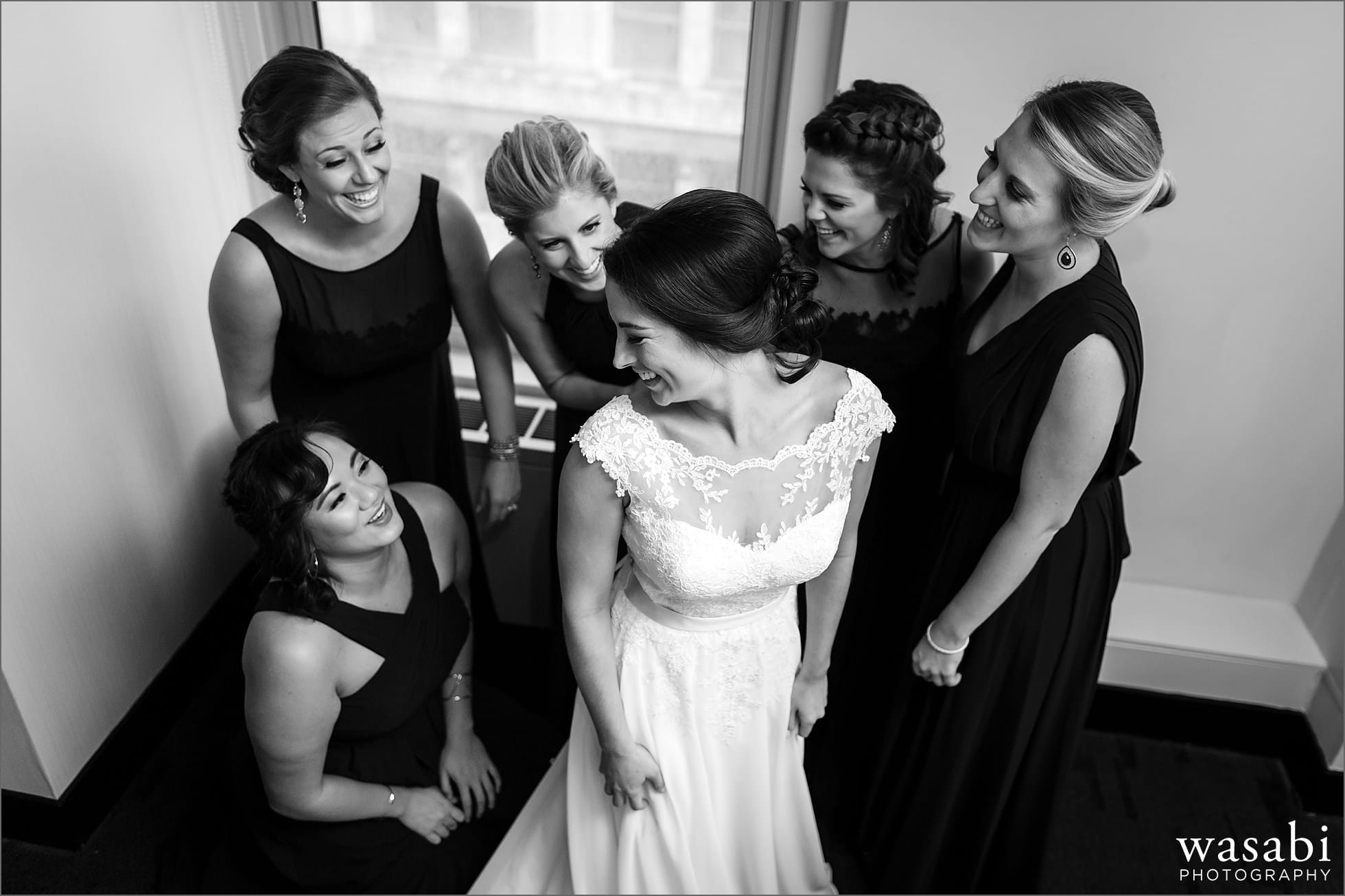 bridesmaids helping bride put on dress w hotel