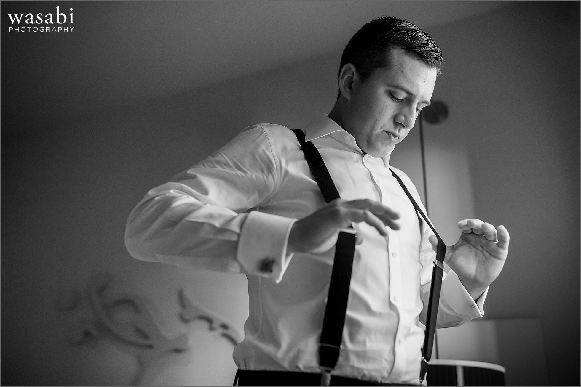 groom puts on suspenders wedding photos