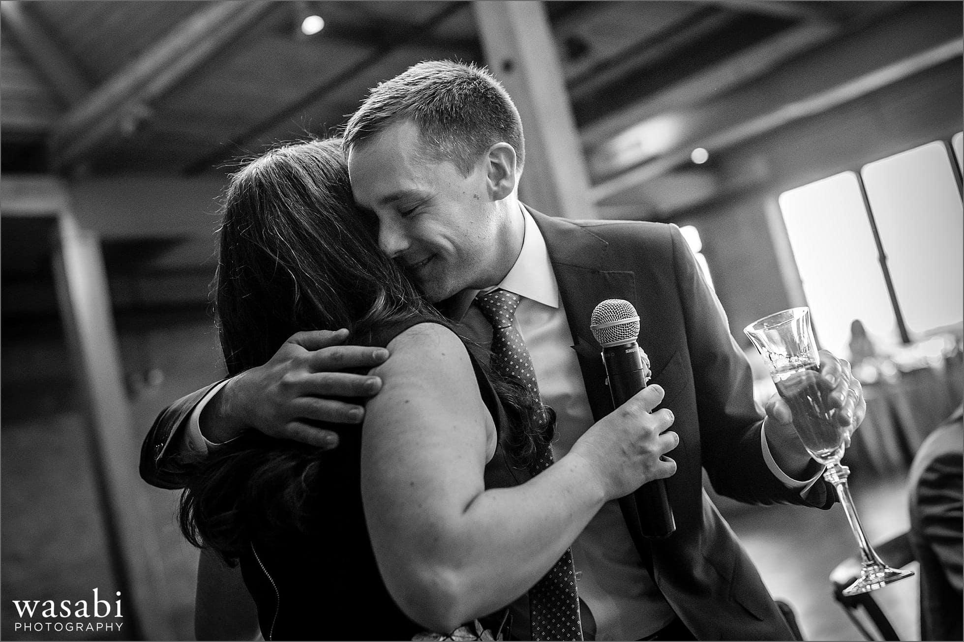 groom hugs best woman after her toast during wedding reception at Skyline Loft at Bridgeport Art Center