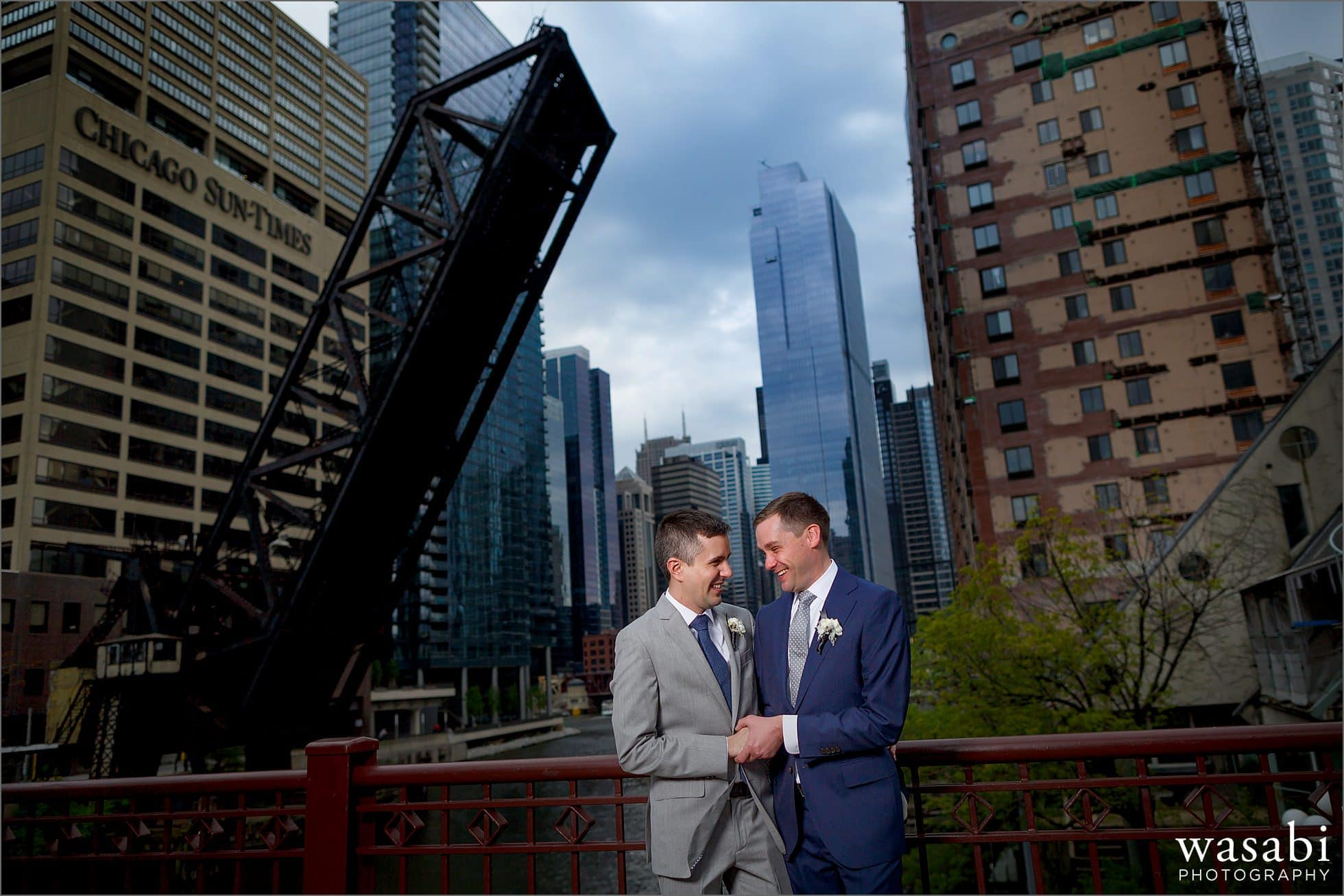 grooms hold hands during a wedding portrait on Kinzie Street Bridge with the Chicago skyline in the background