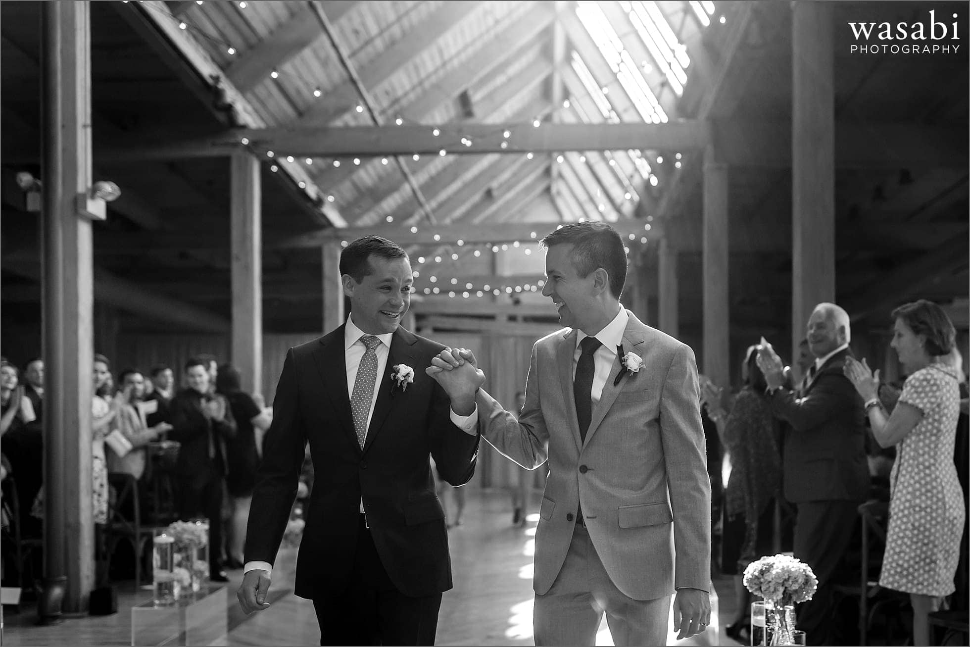 grooms hold hands walking down the aisle after being married at Bridgeport Art Centers Skyline Loft