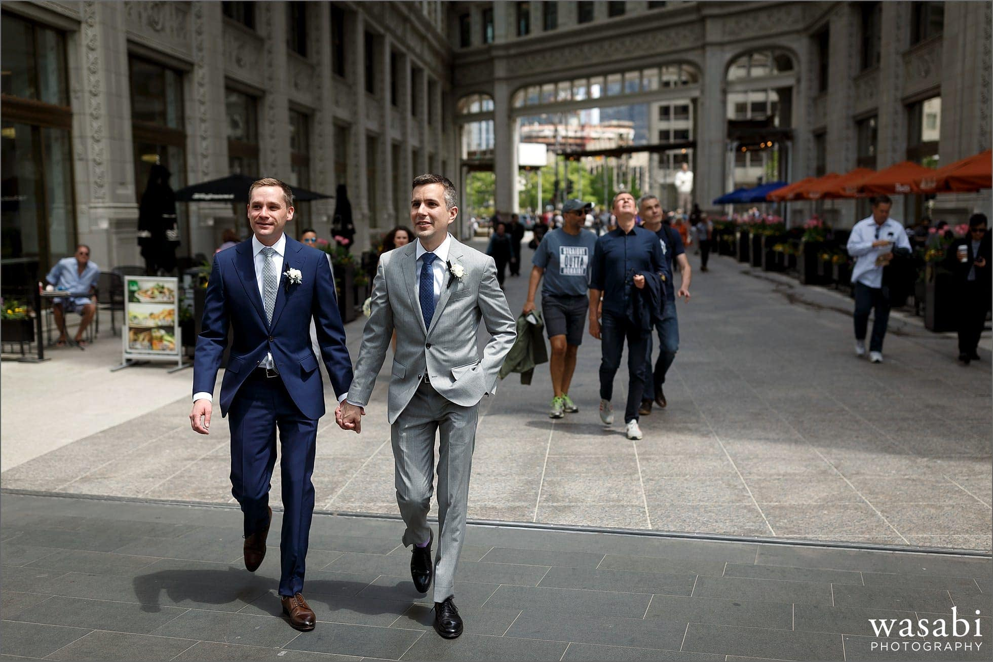grooms hold hands while walking near Wrigley Building in downtown Chicago on their wedding day