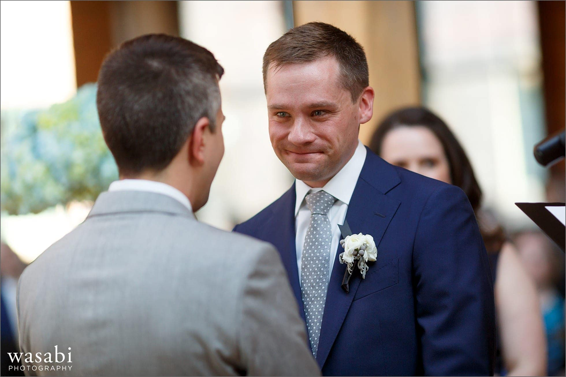 grooms look at each other during wedding ceremony