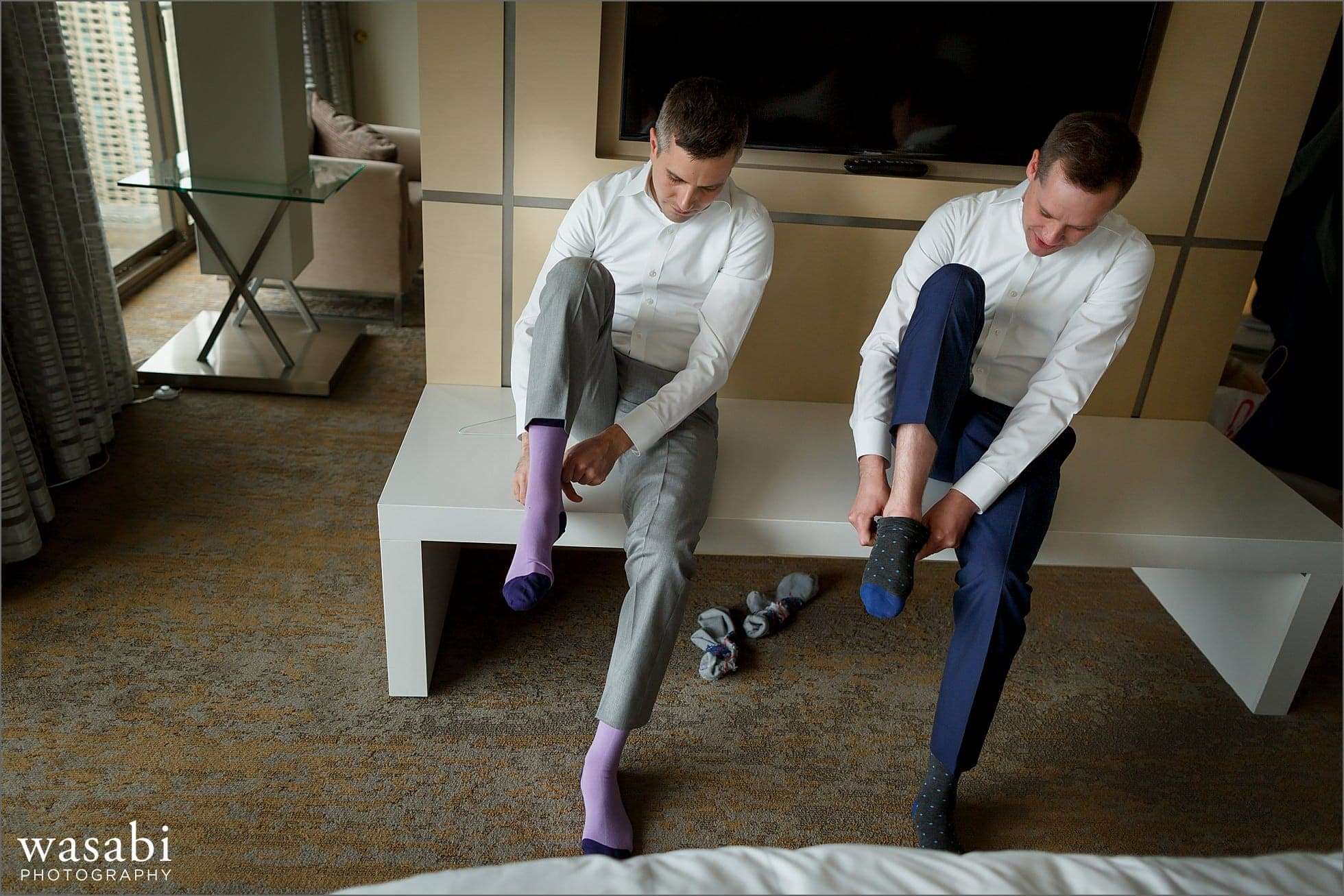 grooms put on socks while getting ready at marriott magnificent mile in chicago for their wedding at bridgeport art center