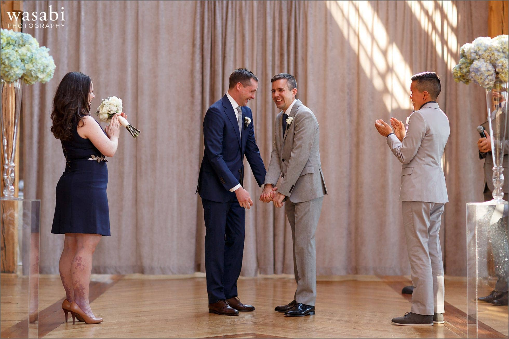grooms react after being anounced husbands during wedding ceremony at Bridgeport Art Center