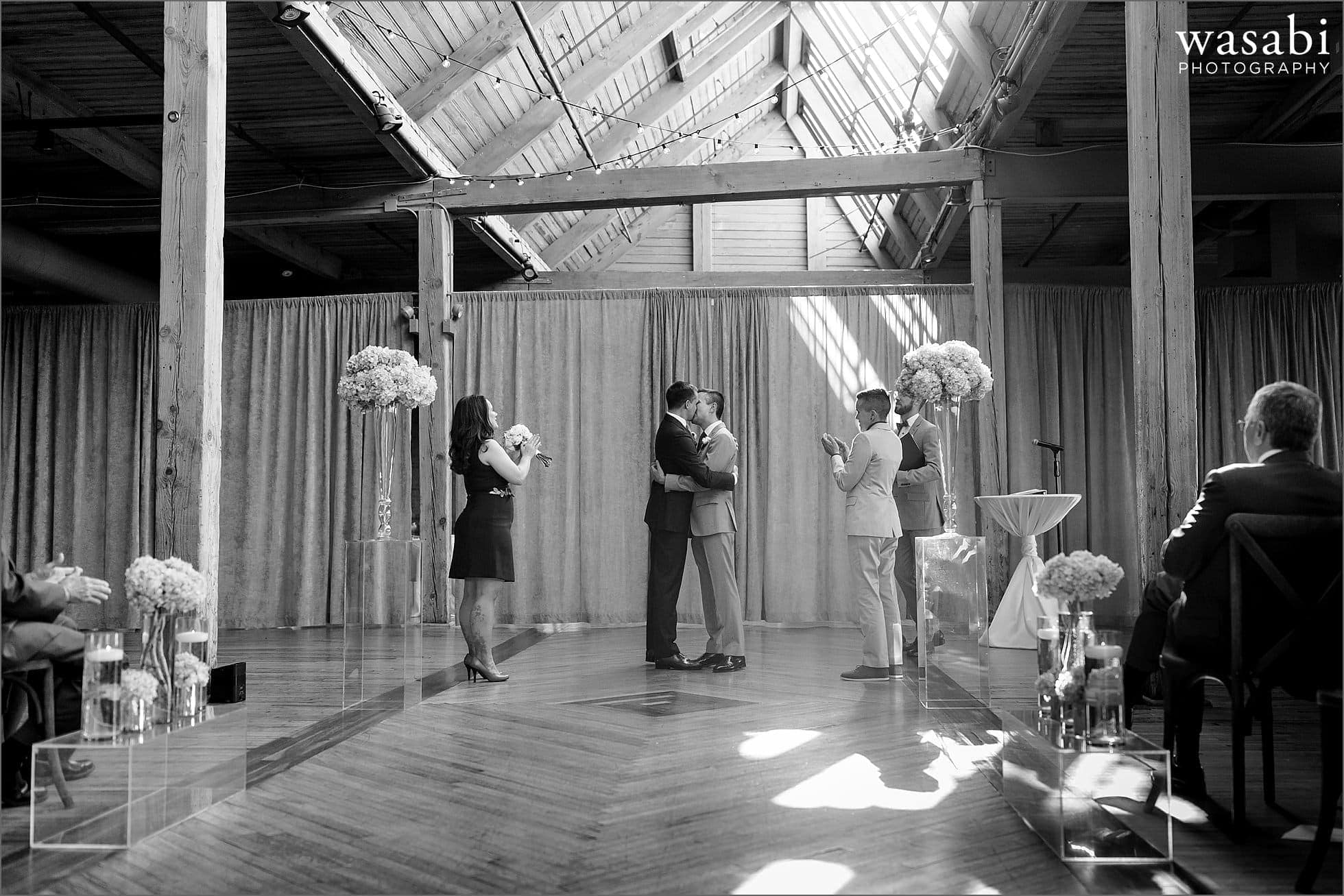 grooms share a first kiss at Bridgeport Art Centers Skyline Loft in Chicago
