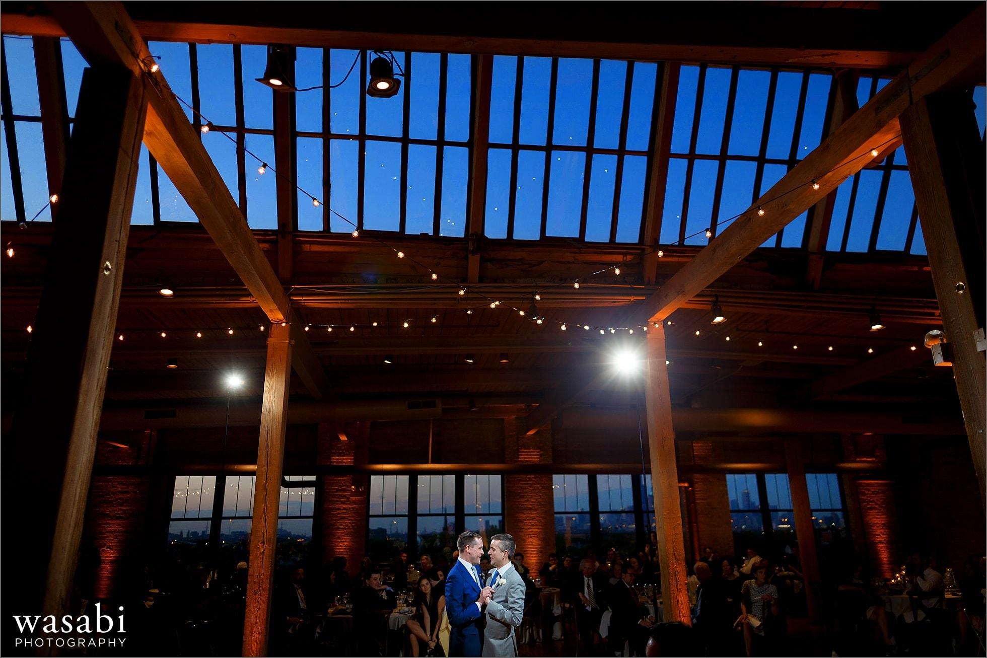 grooms share their first dance during their wedding reception at Bridgeport Art Centers Skyline Loft