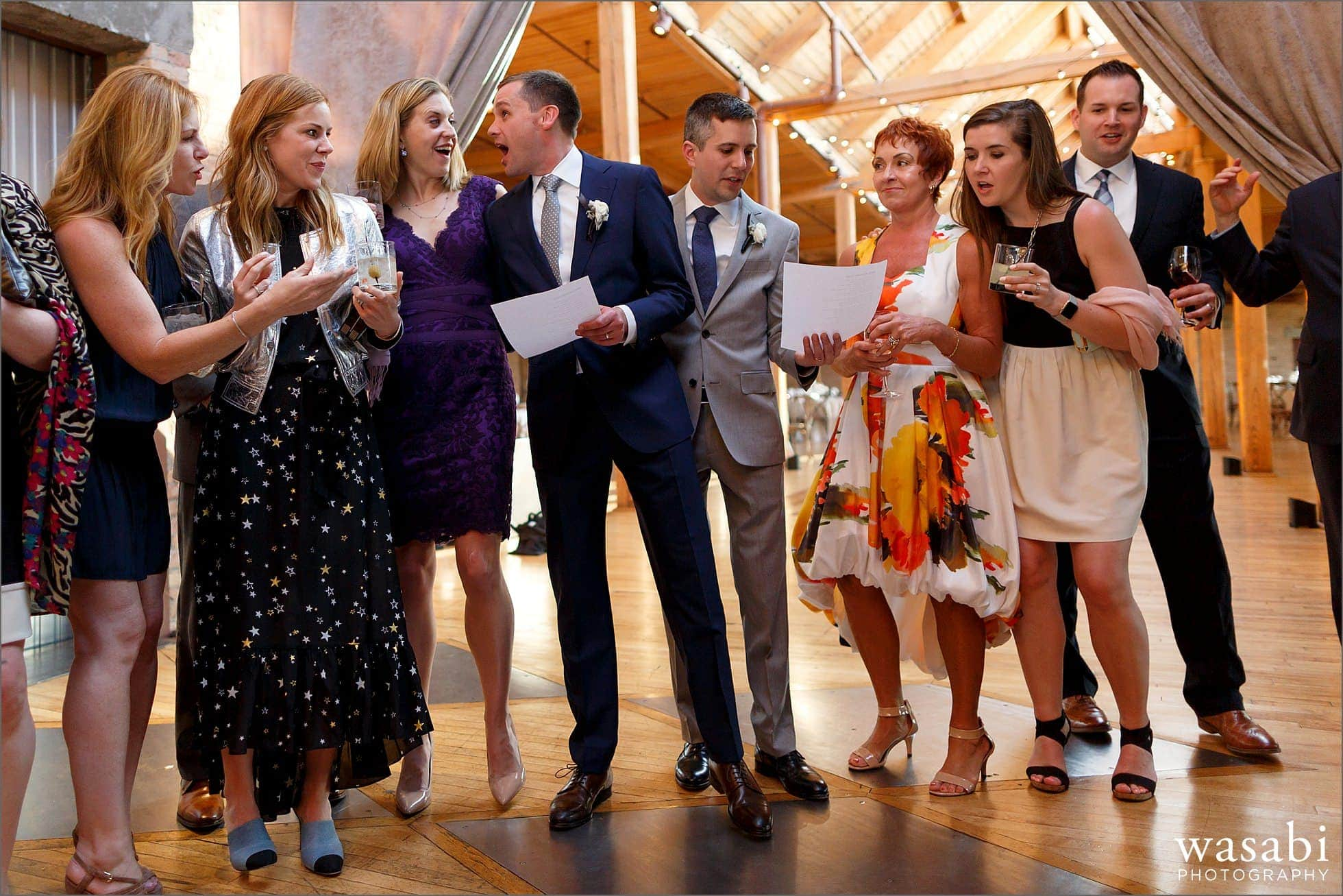 grooms sing Mack the Knife with guests during their Bridgeport Art Center Skyline Loft wedding reception