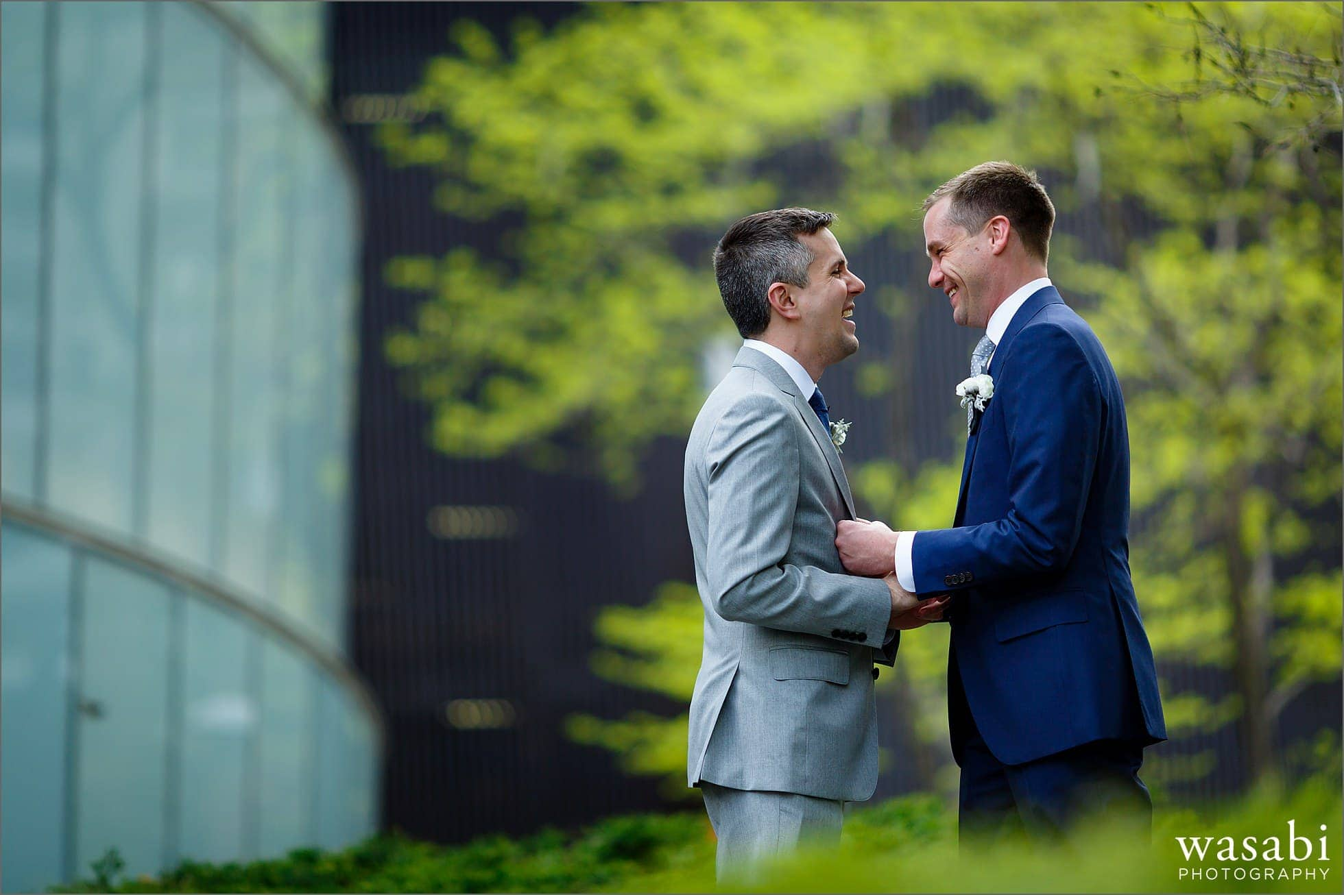 two grooms embrace in a park near Trump Tower in downtown Chicago on their wedding day