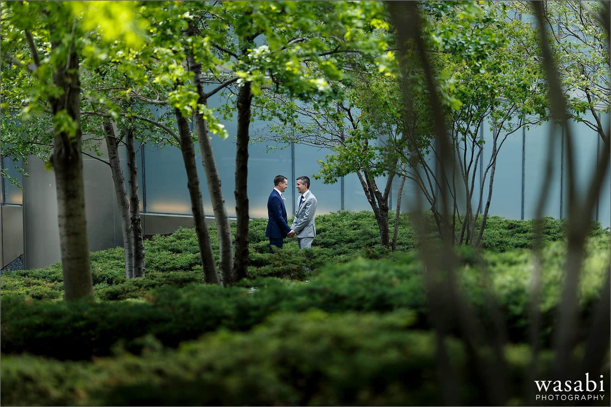 two grooms hold hands under trees near Trump Tower in downtown Chicago on their wedding day