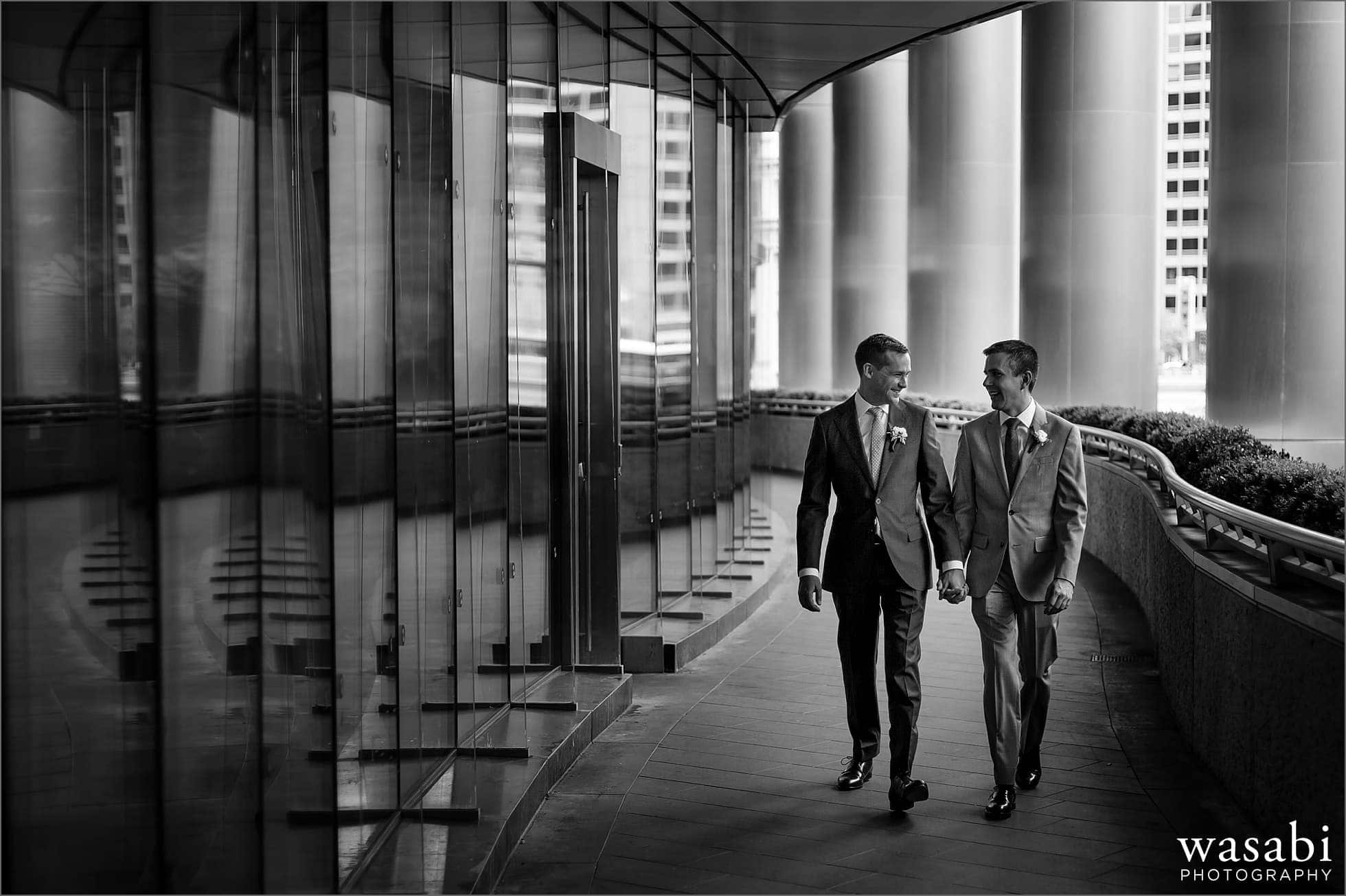 two grooms hold hands while walking next to Trump Tower in Chicago before their wedding at Bridgeport Art Center
