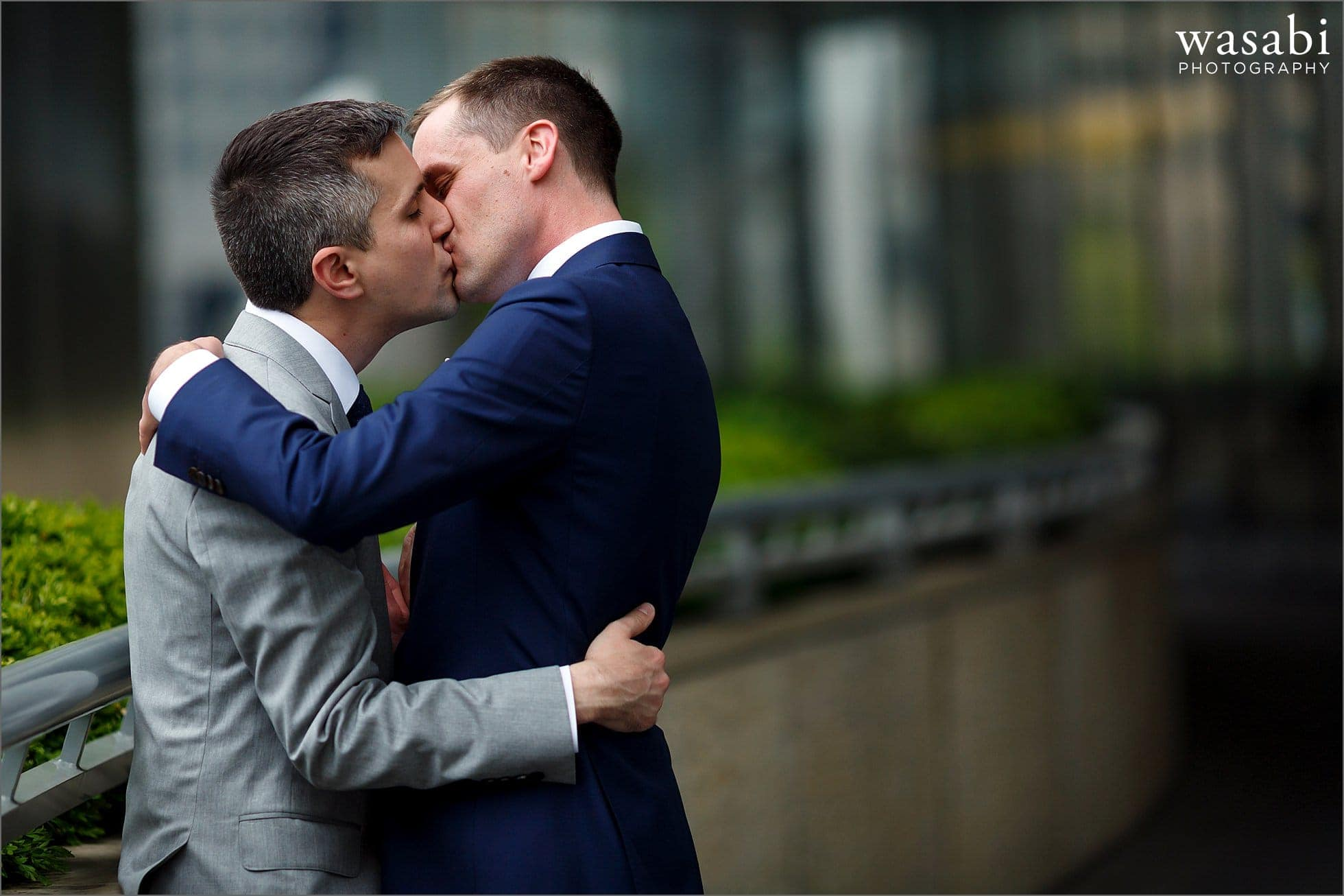 two grooms kiss during portraits before their wedding in Chicago