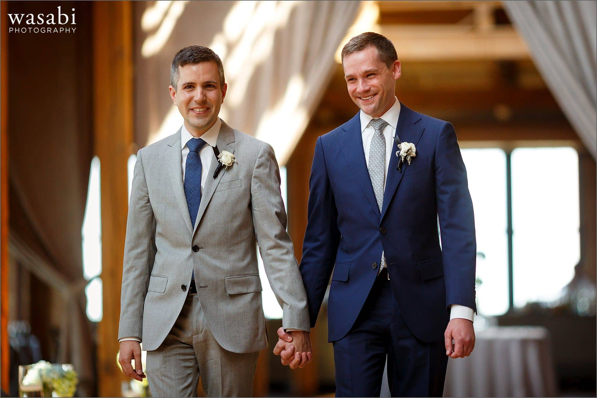 two grooms walk down the aisle during their wedding ceremony at Skyline Loft at Bridgeport Art Center in Chicago