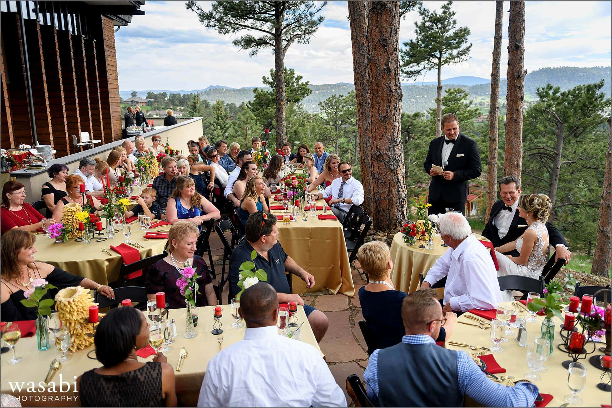 best man toasts the couple during their home wedding reception on lookout mountain in Golden Colorado with the Rocky Mountain range in the background