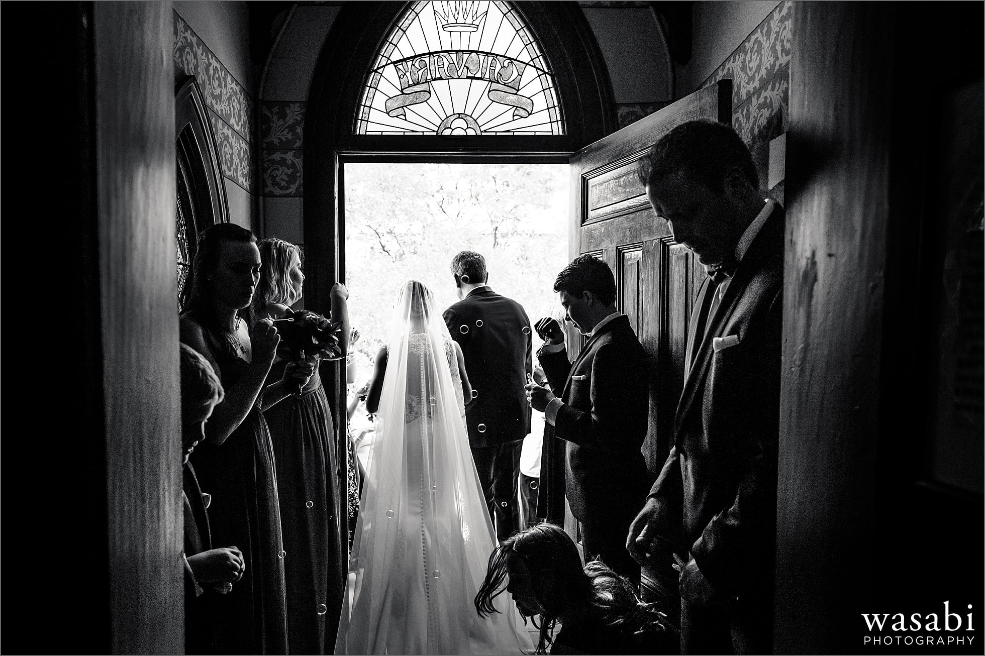 black and white photo from behind of bride and groom walking out to bubbles after their wedding ceremony at Calvary Church in downtown Golden Colorado