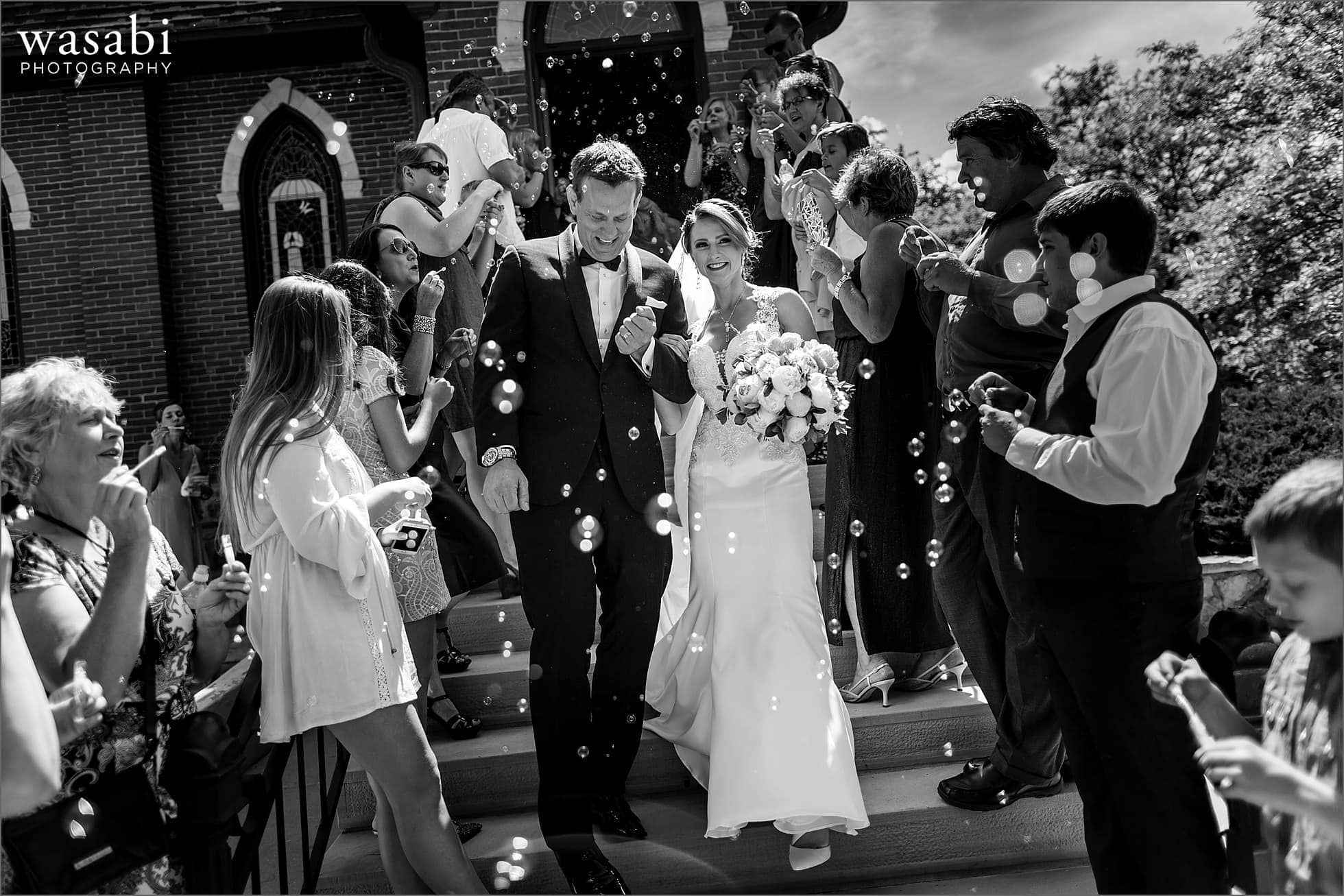 black and white photo of bride and groom walking out to bubbles after their wedding ceremony at Calvary Church in downtown Golden Colorado