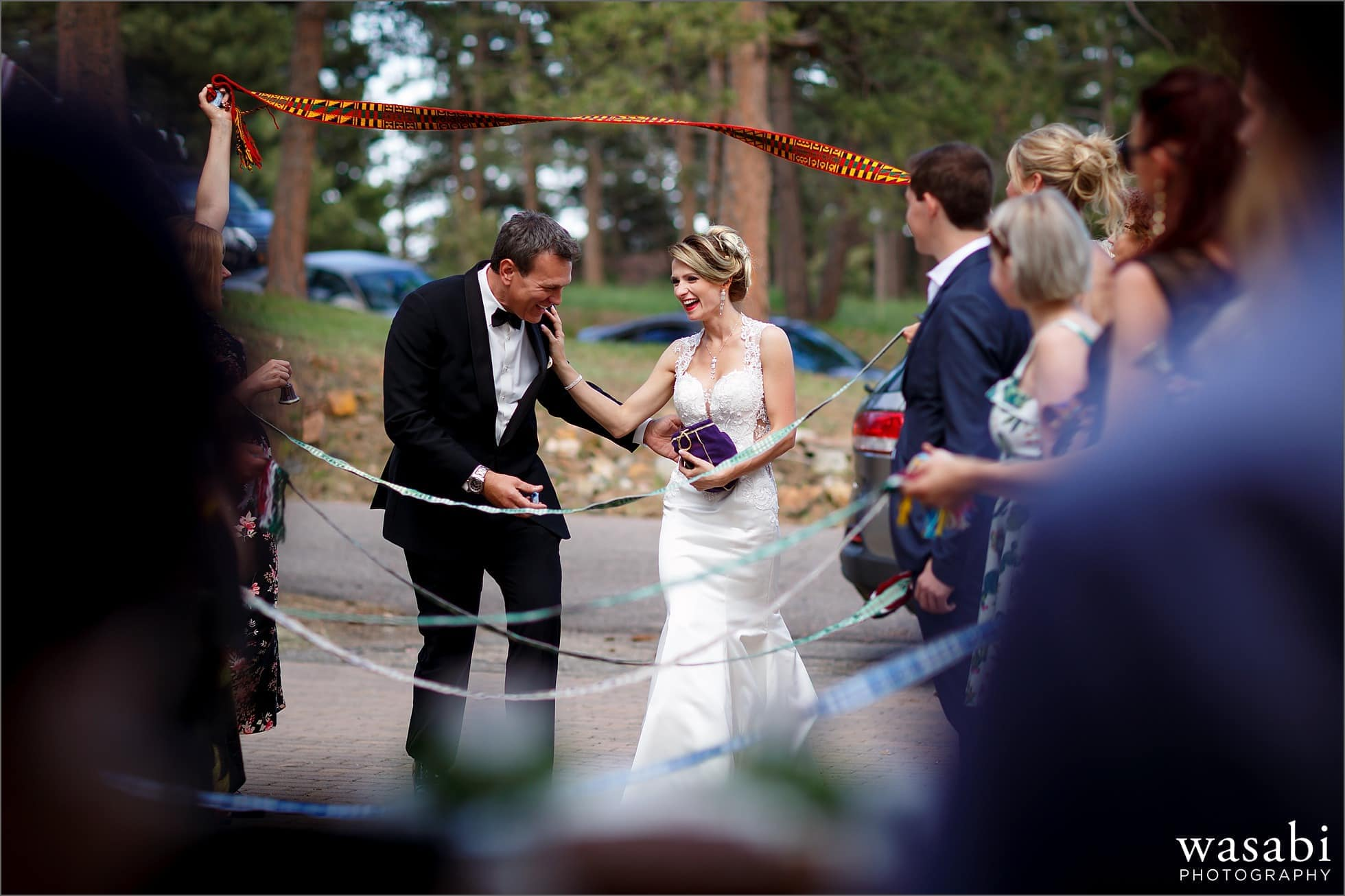 bride and groom arrive to their home wedding reception to a Lithuanian wedding tradition with their friends and family holding woven sashes