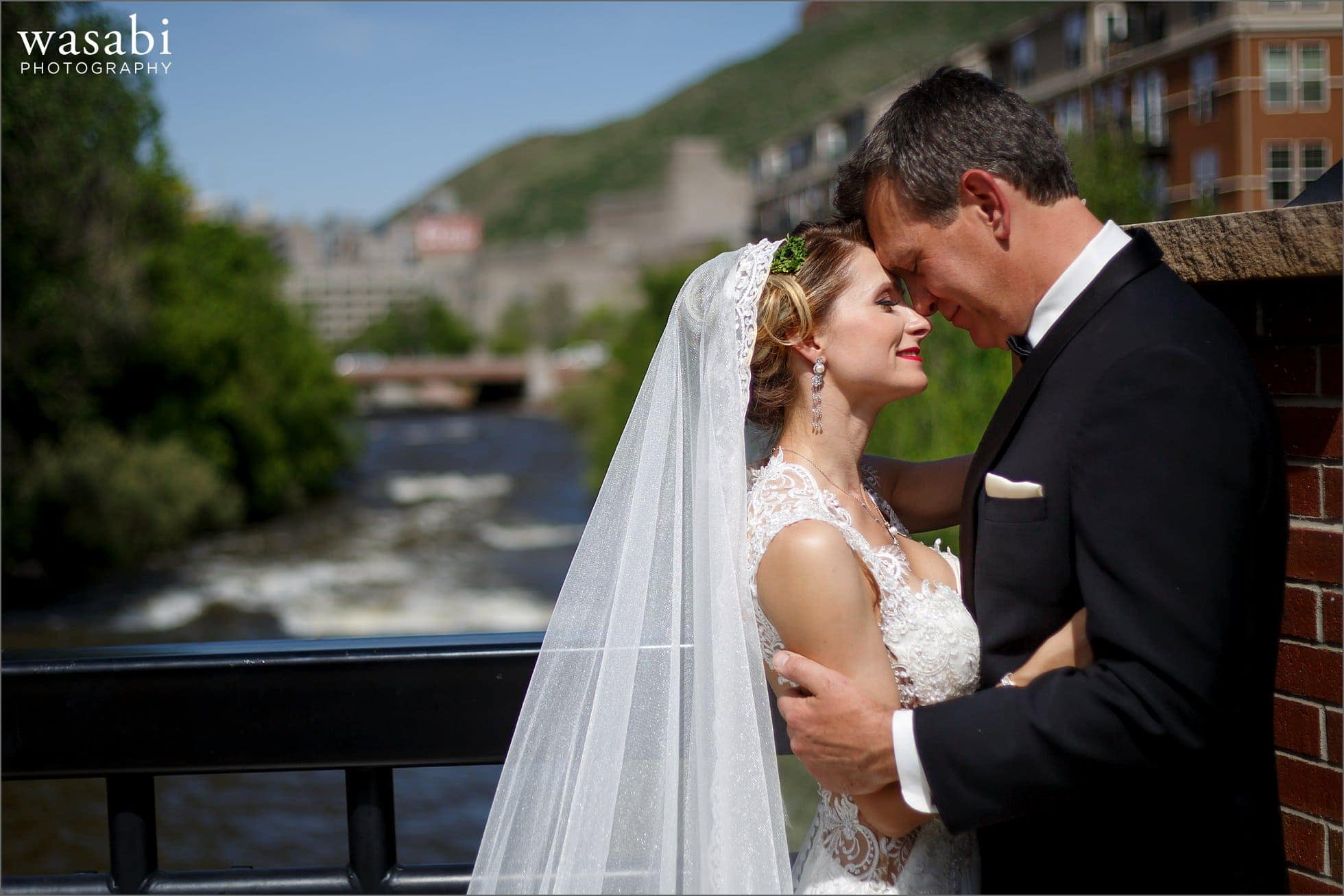 bride and groom pose for portrait on bridge with coors brewery in background in downtown Golden Colorado