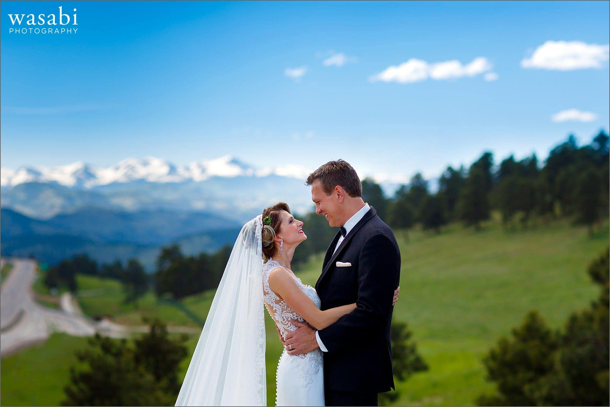 bride and groom pose photo on bride over I-70 near buffalo park overlook with the rocky mountain range in the background