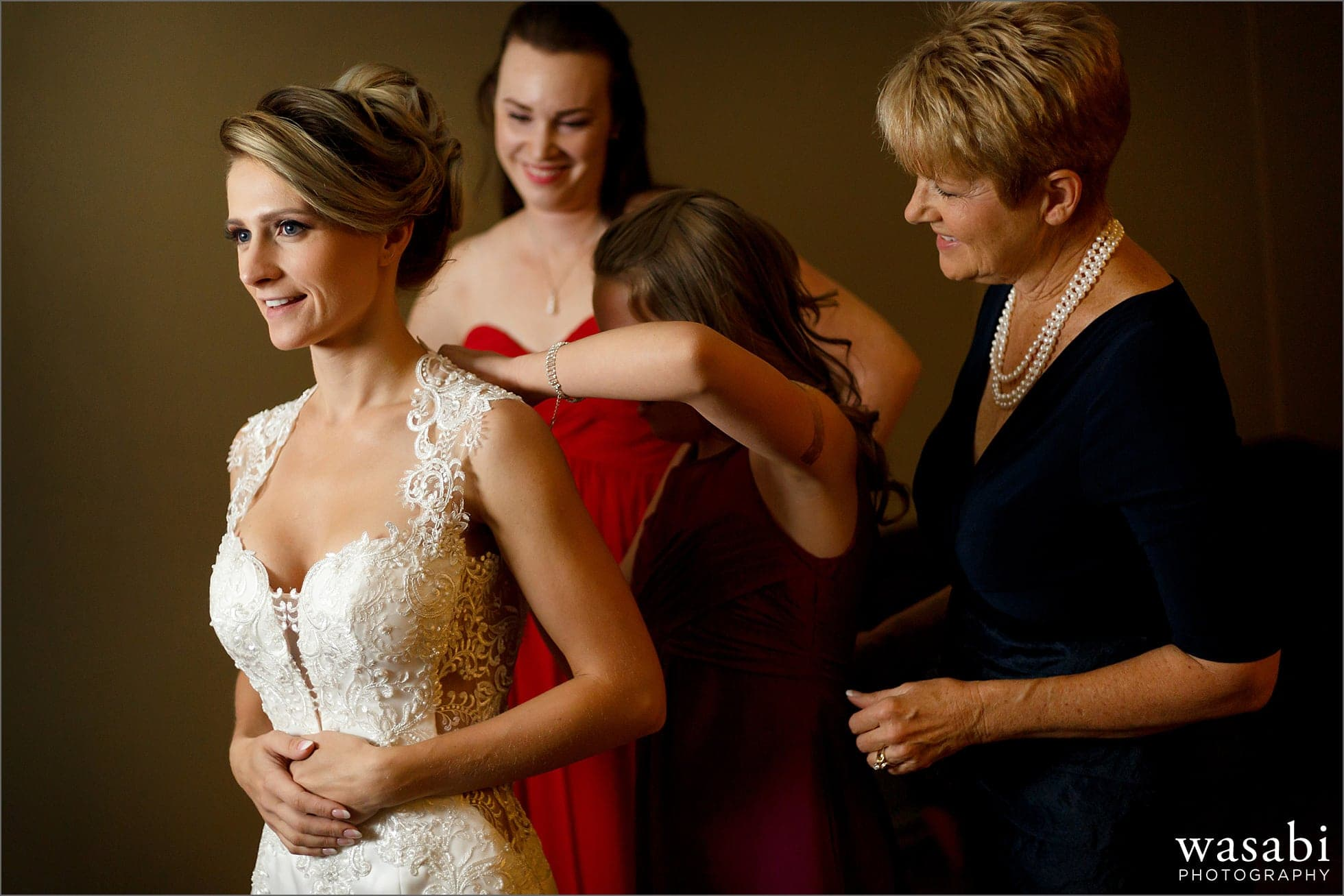 bridesmaids and mom help bride into her dress while getting ready for her Golden Colorado wedding