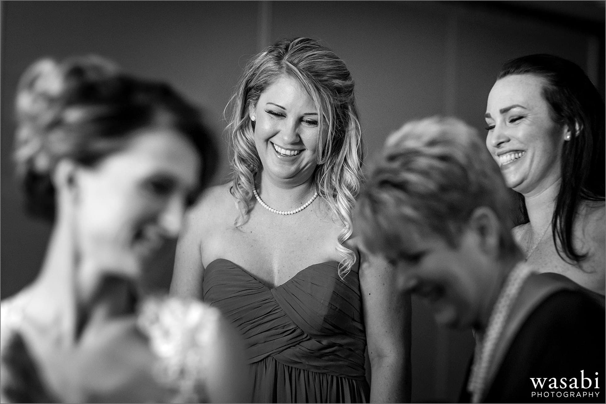bridesmaids laugh while watching mom help bride into her dress for a Golden Colorado wedding