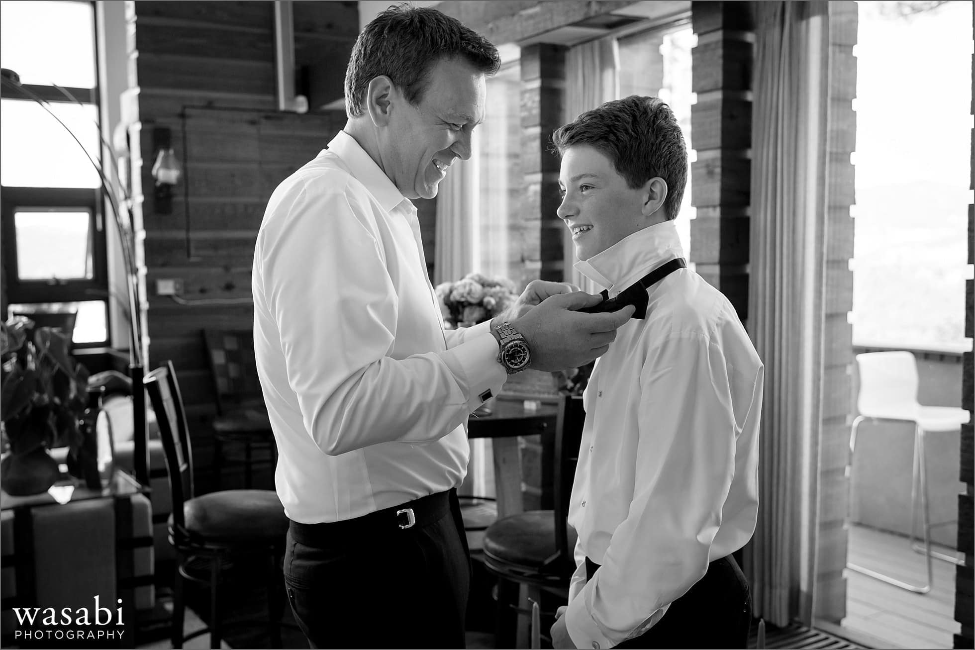 groom helps son put on bow tie while getting ready for his wedding at their home on lookout mountain in Golden Colorado