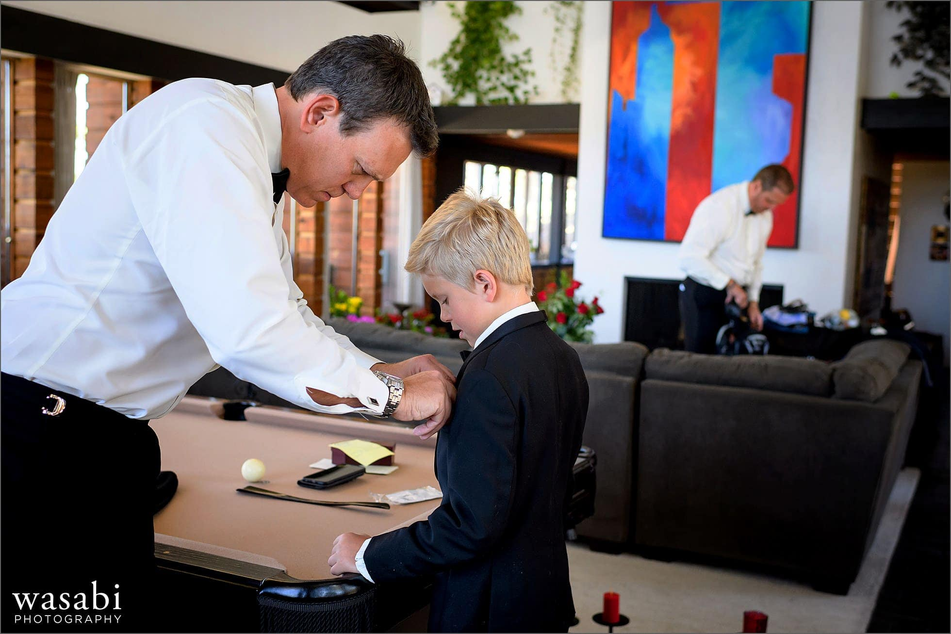 groom helps son with his pocket square while getting ready for his wedding at their home on lookout mountain in Golden Colorado