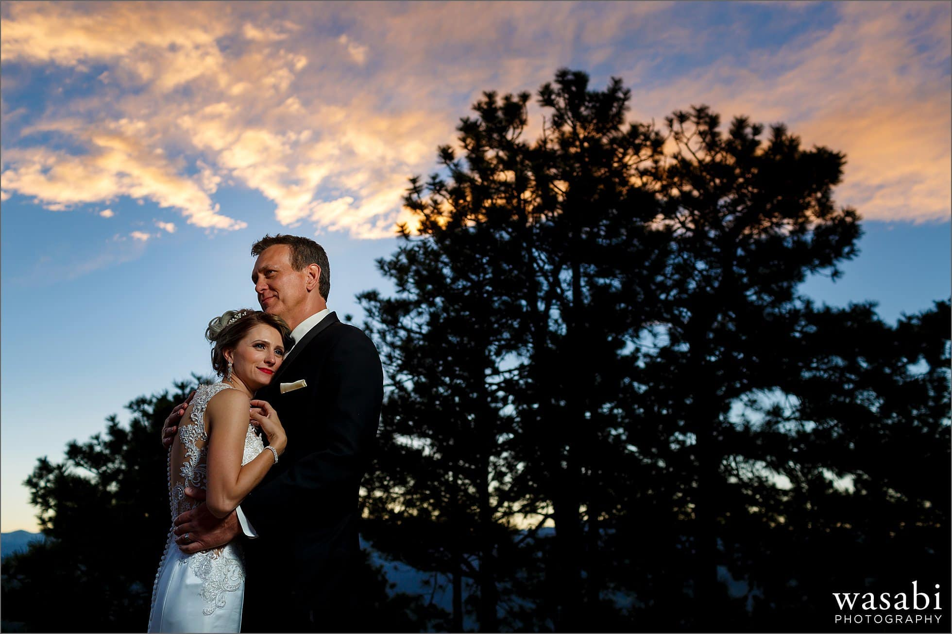 trees and blue sky portrait with clouds of bride in groom on Lookout Mountain in Golden Colorado