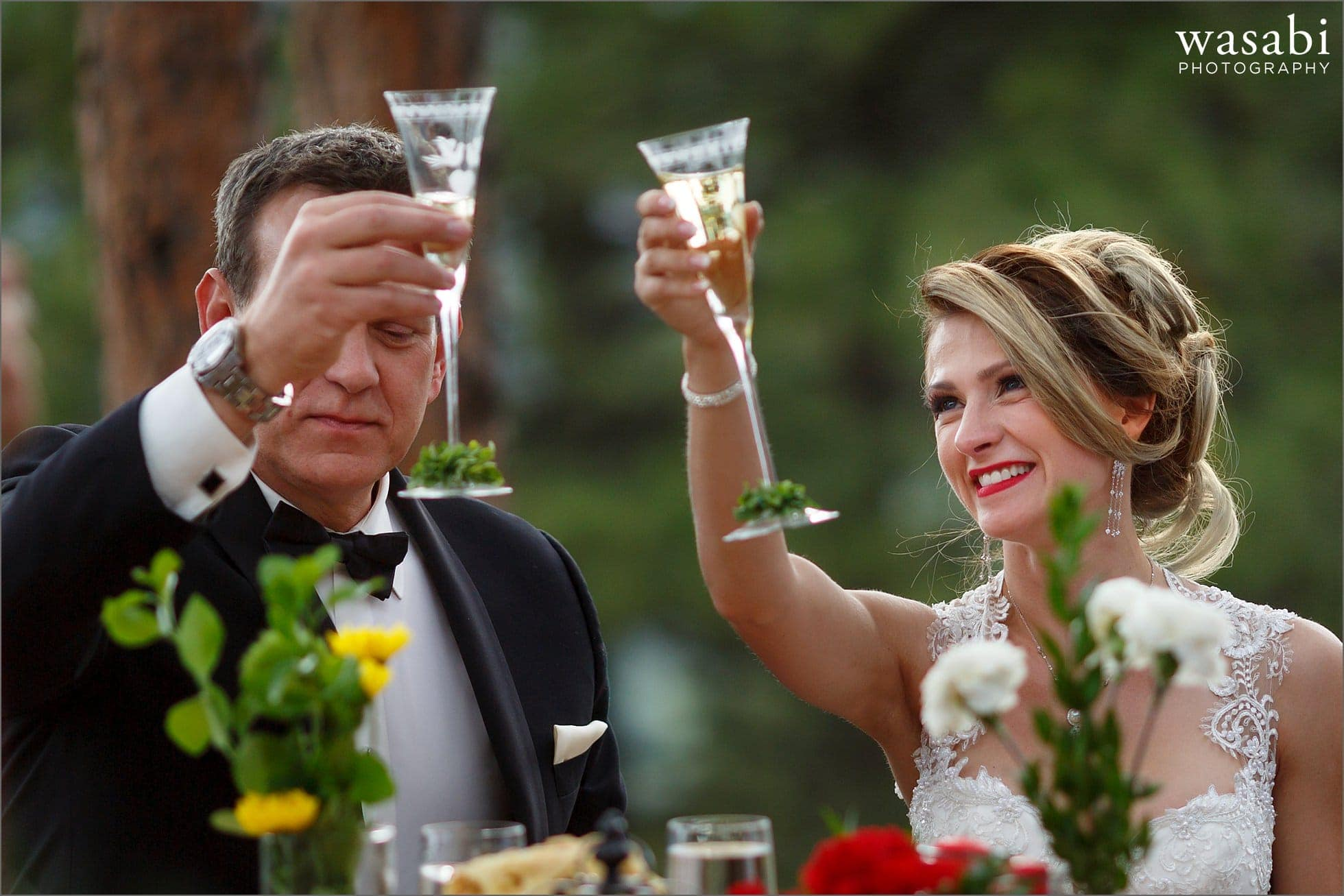 wedding couple raises their glasses during a toast at their home wedding reception on lookout mountain in Golden Colorado