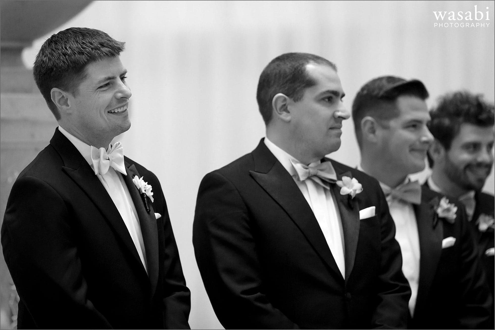 Groom reacts as bride walks down aisle during a wedding ceremony at The Rookery Building in Chicago