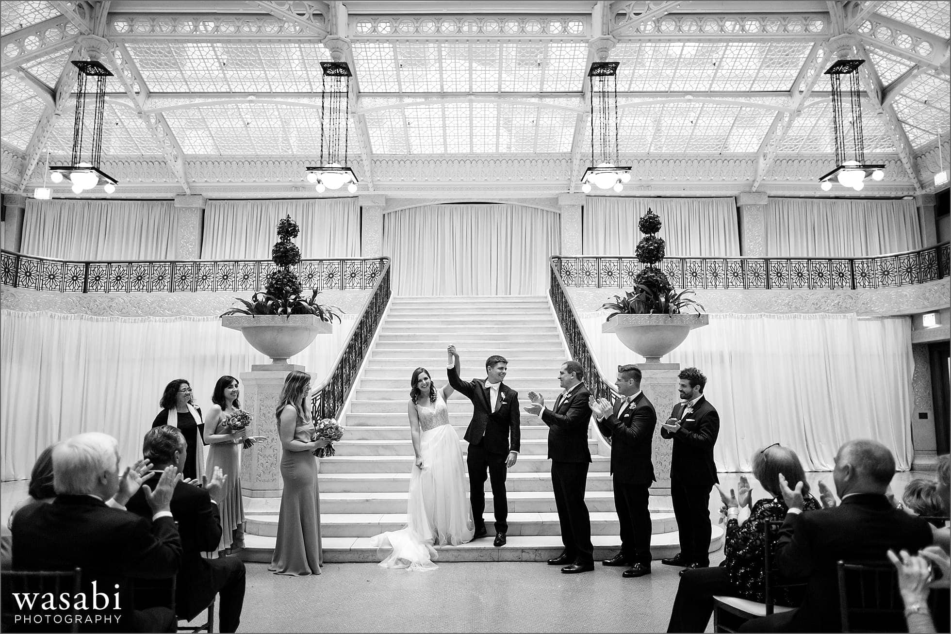 The Rookery Building wedding photos with wide angle view of bride and groom celebrating after being married at The Rookery Building in Chicago