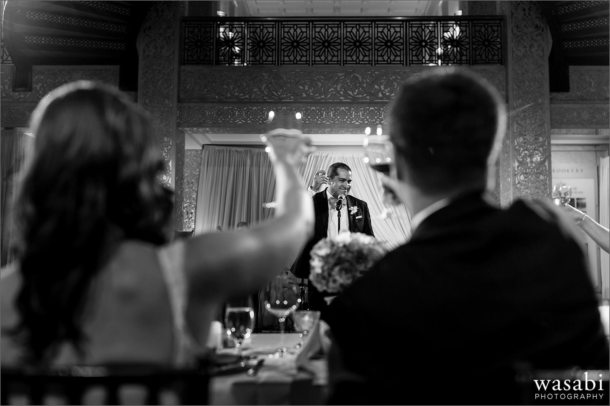best man toast speech with bride and groom raising glasses in the forground at The Rookery Building in Chicago