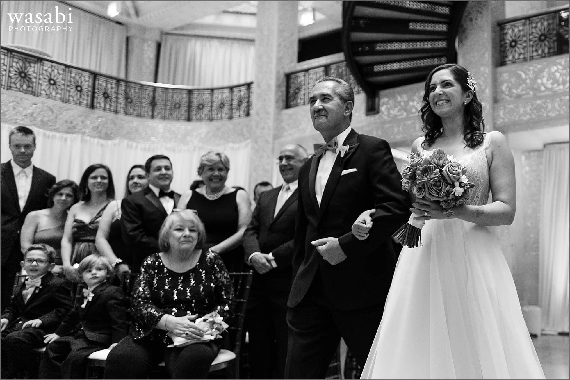 bride and father walk down the aisle during a wedding ceremony at The Rookery Building in Chicago