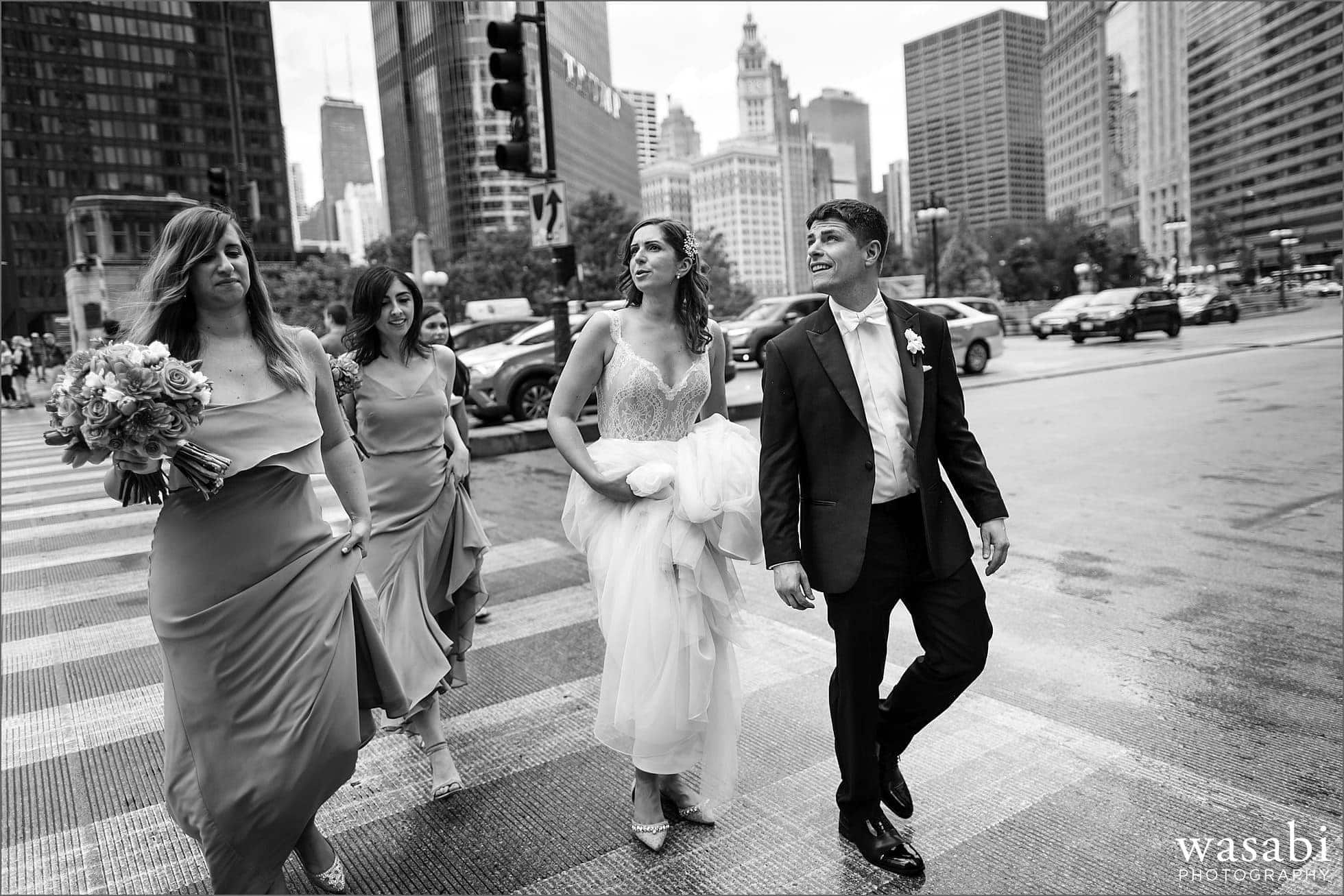 bride and groom and wedding party walk across Wacker Drive on State Street on their wedding day