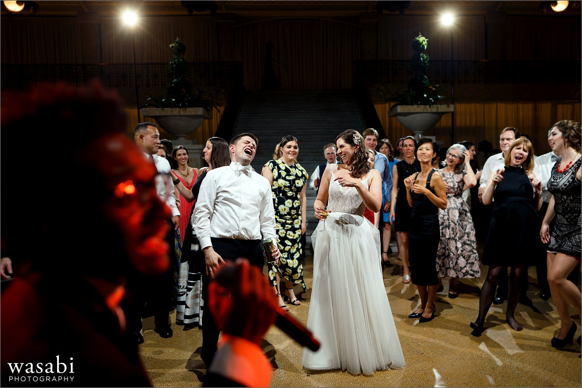 bride and groom dance with band singing in the forground during wedding reception at The Rookery Building in Chicago