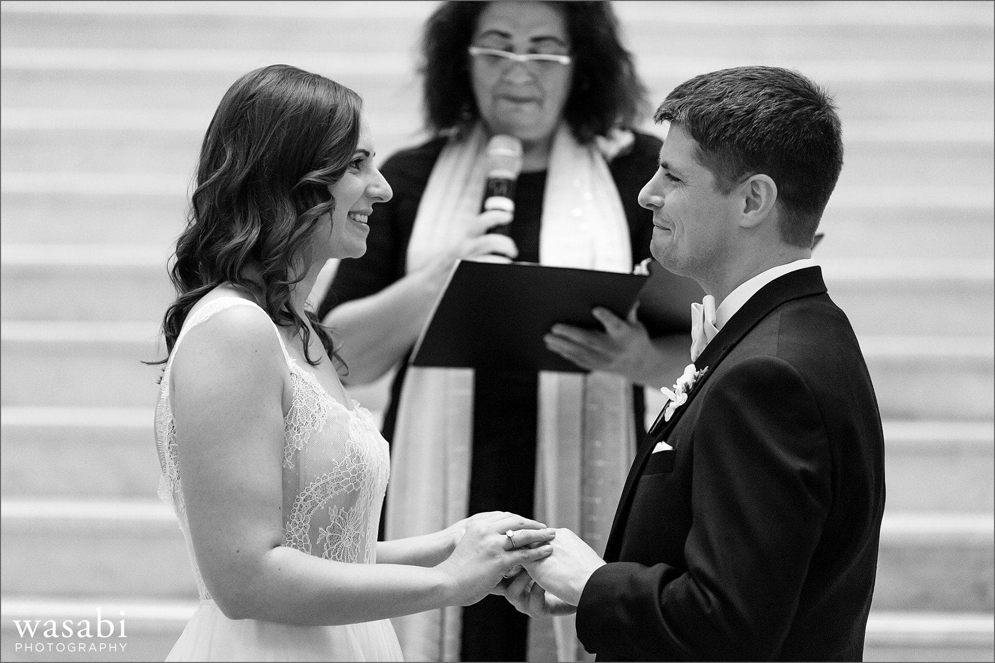 bride and groom exchange rings during wedding ceremony at The Rookery Building in Chicago