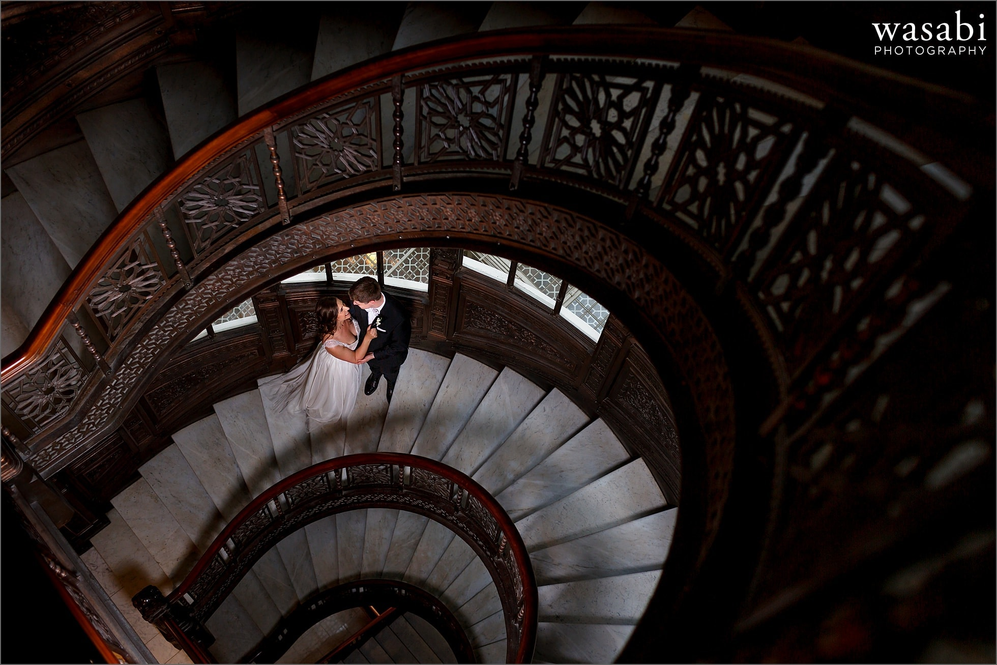 bride and groom pose for The Rookery stairs wedding photos before their wedding ceremony