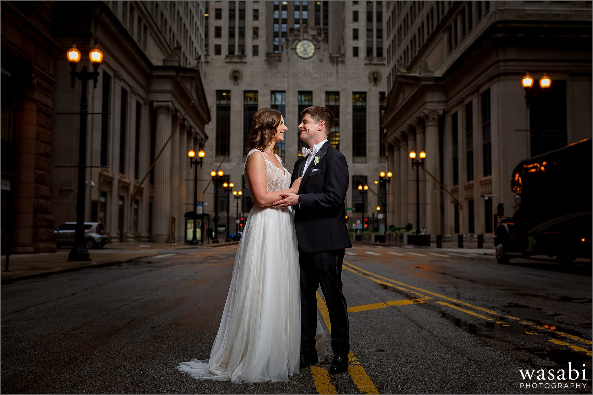 bride and groom pose for portait in front of the Chicago Board of Trade building before their wedding at The Rookery Building