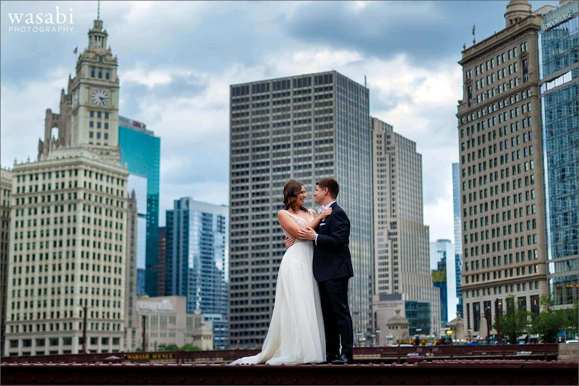 bride and groom pose on top of State Street bridge for a wedding portrait