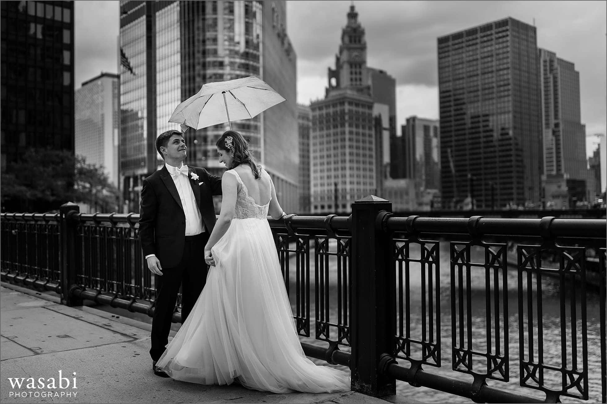 bride and groom stand under an umbrella during a rainy wedding day on State Street bridge