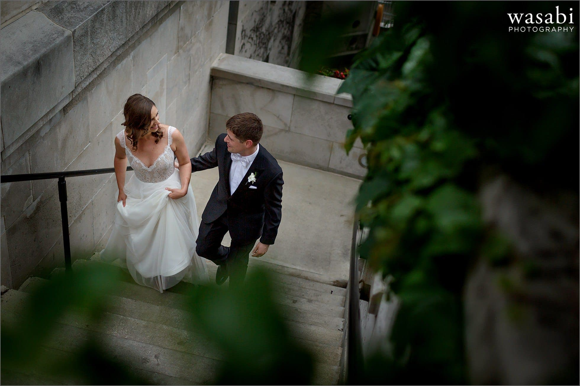 bride and groom walk up stairs from Chicago riverwalk to Wacker Street and State Street