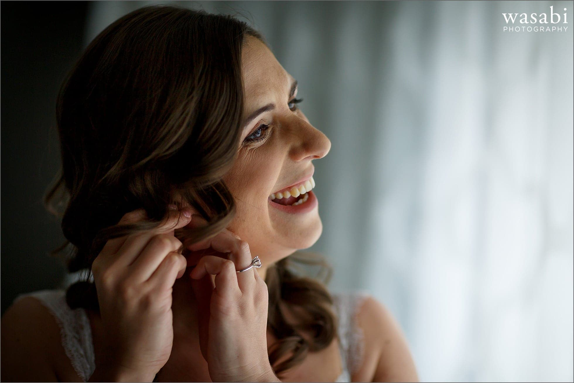 bride puts in earring while getting ready for her wedding at Renaissance Chicago Downtown Hotel