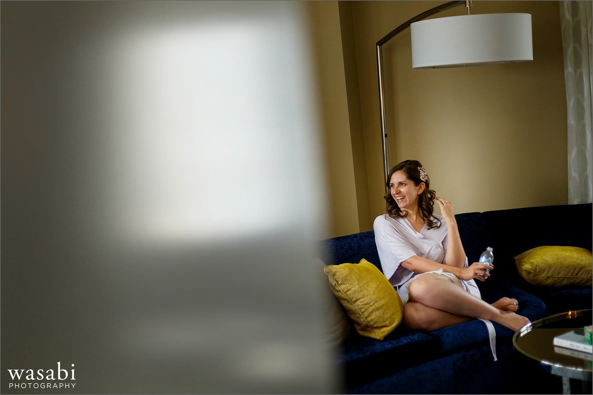 bride sits on couch while getting ready at Renaissance Chicago Downtown Hotel for her wedding