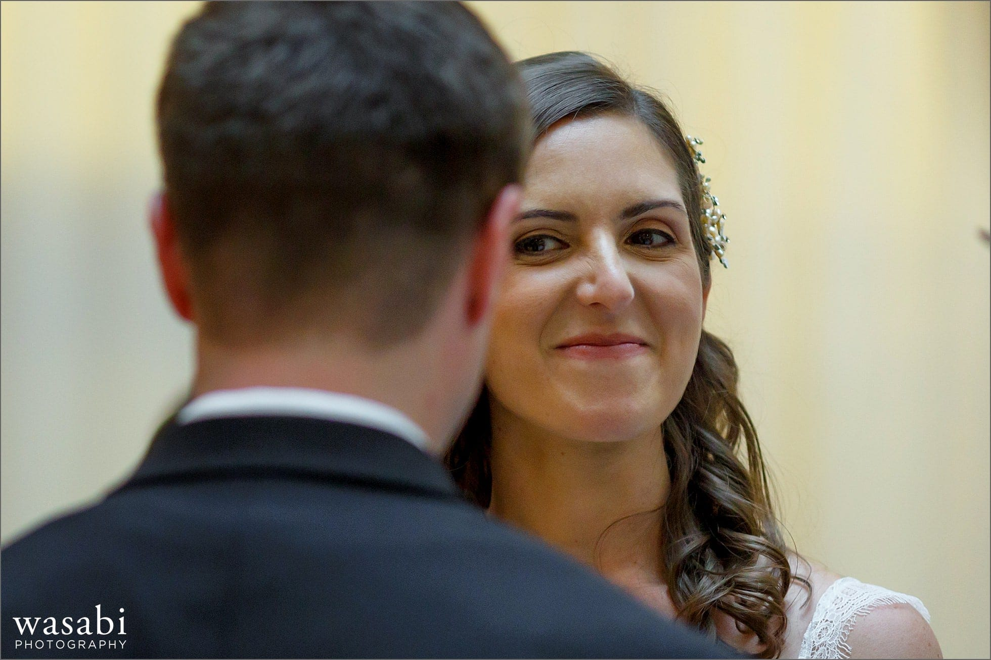 bride smiles at her groom during wedding ceremony at The Rookery Building in Chicago