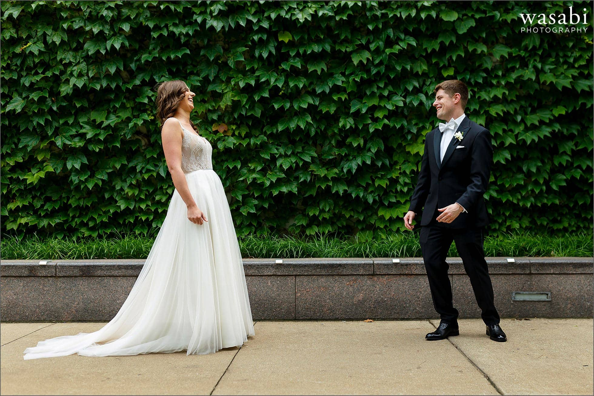 first look reaction on Chicago riverwalk with ivy in the background as bride and groom see each other for the first time on their wedding day