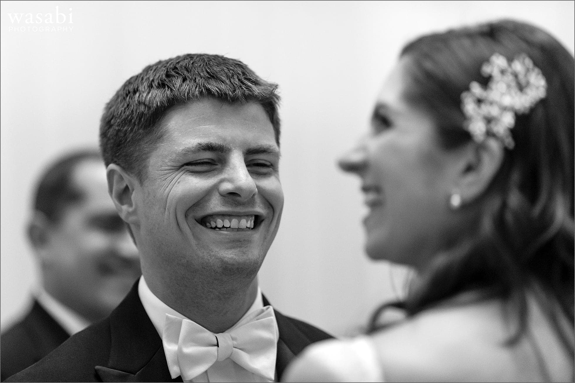 groom laughs with bride during their wedding ceremony at The Rookery Building in Chicago