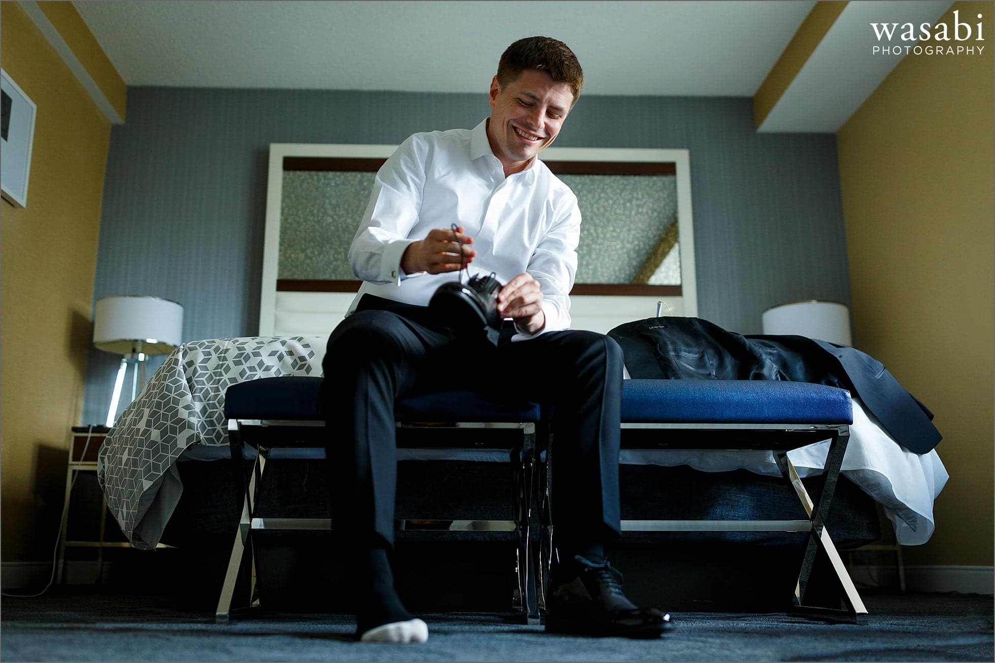 groom puts on his shoes while while getting ready for his wedding at Renaissance Chicago Downtown Hotel