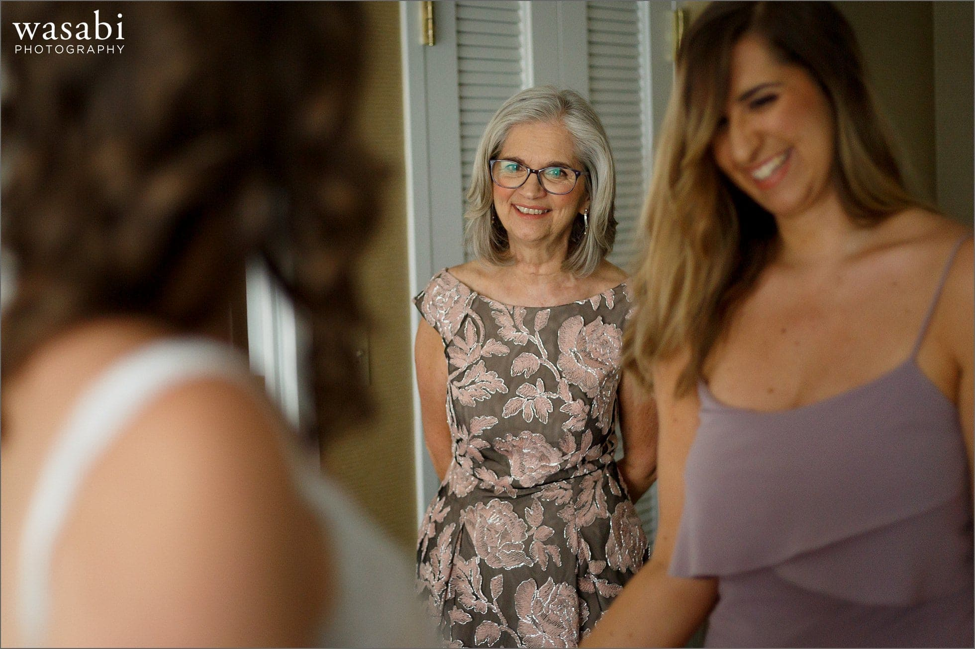 mother and bridesmaid react after seeing bride in her dress while getting ready for her wedding at Renaissance Chicago Downtown Hotel